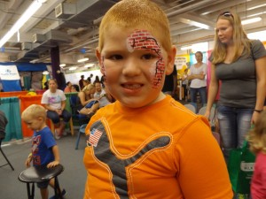 A boy with bricks painted on his face.