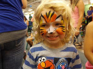 A little girl painted as a cute tiger