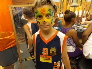 A brightly colored lizard face painting on a boy