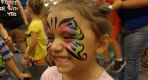 A pink and blue Denver Face Painting butterfly with a huge smile