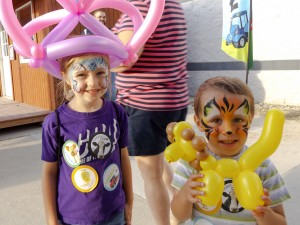 Princess face paint and balloon crown along with a tiger face paint and balloon