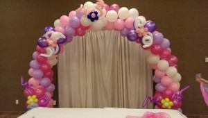 A balloon arch with flowers attached all over