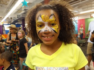A young girl painted as a cheetah