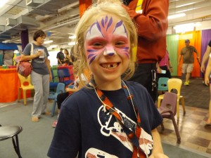 A pink and purple tiger with a big smile and face painting!