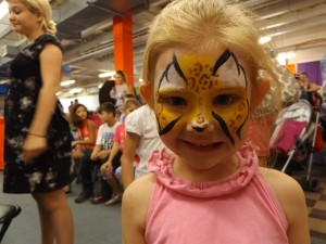 A smiling young girl painted as a cheetah.