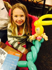 a little girl smiling with a balloon animals mermaid
