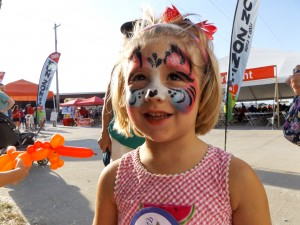 A kitten face painting and a unicorn balloon animal at a festival in Denver